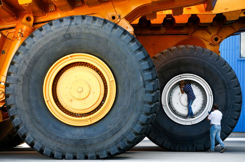 People take a selfie at the wheels of BelAZ dump trucks at the Belarusian Autoworks manufacturer in Zhodino, Belarus August 27, 2019.