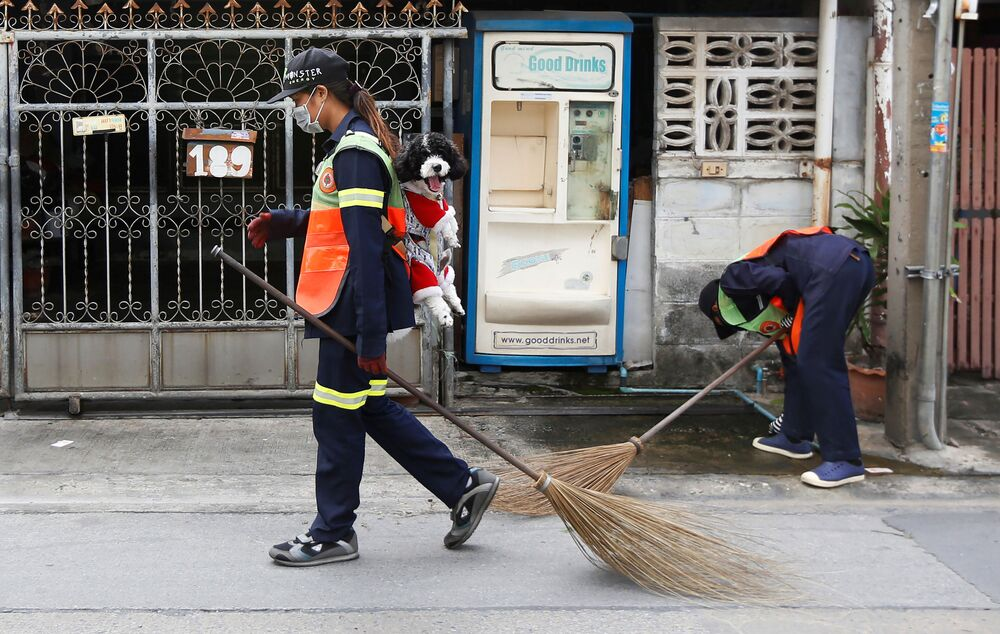 Thitirat Keowa-ram, Bangkok's street sweeper, carries her 1-year old poodle-shih tzu mix breed as she works at a street in Bangkok, Thailand, August 28, 2019.