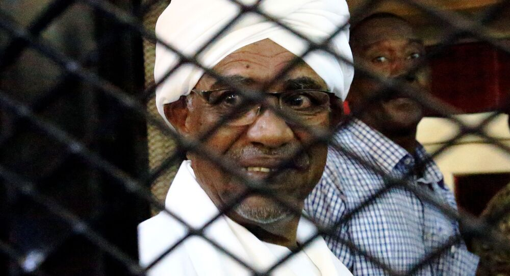 Sudan's former president Omar Hassan al-Bashir smiles as he is seen inside a cage at the courthouse where he is facing corruption charges, in Khartoum, Sudan August 31, 2019
