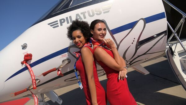 Girls posing for photos in front of the Swiss Pilatus PC-24 business jet at the MAKS-2019 international aviation and space show in Zhukovsky outside Moscow.  - Sputnik International