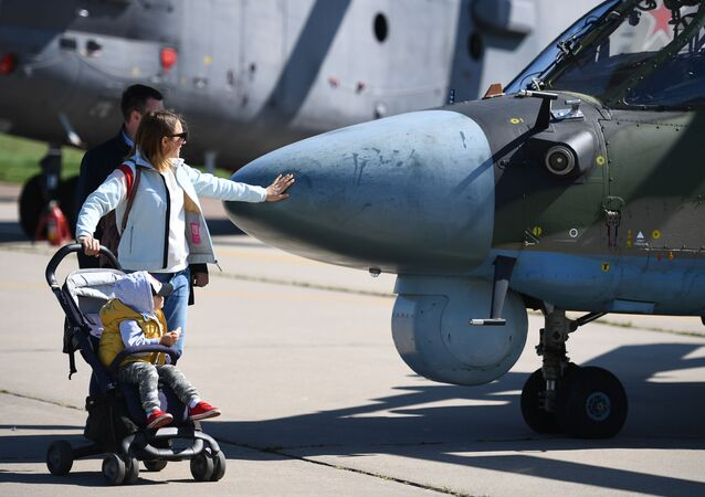Visitors pass by a Ka-52 Alligator military helicopter on display at the MAKS-2019 International Aviation and Space Show in Zhukovsky, outside Moscow, Russia.