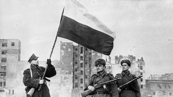 Soviet troops pose as Polish soldier raises Polish flag over Warsaw in January 1945. The liberation of Poland cost the Red Army 600,000 casualties. - Sputnik International