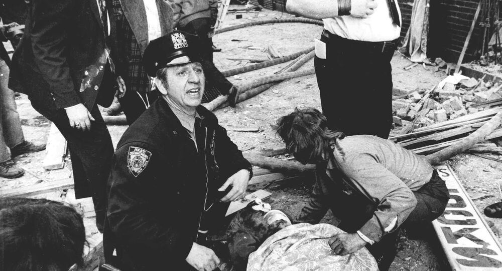A police officer calls for help as he kneels near a victim of the Fraunces Tavern bomb in New York in January 1975.