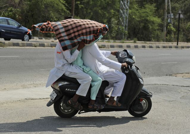 Indian men use a scarf to shield themselves from the sun as they ride a scooter on a hot summer afternoon in Hyderabad, India, Friday, May 17, 2019
