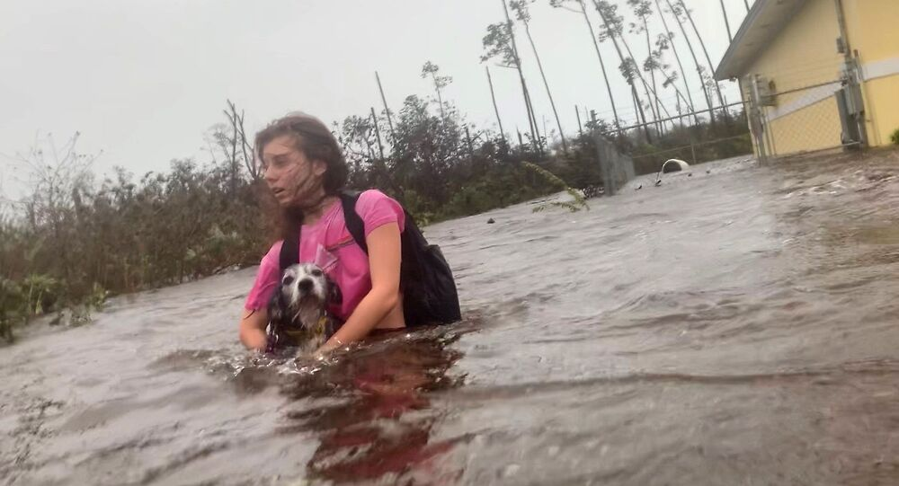 Julia Aylen wades through waist deep water carrying her pet dog as she is rescued from her flooded home during Hurricane Dorian in Freeport, Bahamas, Tuesday, Sept. 3, 2019. Practically parking over the Bahamas for a day and a half, Dorian pounded away at the islands Tuesday in a watery onslaught that devastated thousands of homes, trapped people in attics and crippled hospitals. Julia Aylen is the daughter of Photojournalist Tim Aylen, author of this photo. (AP Photo/Tim Aylen)