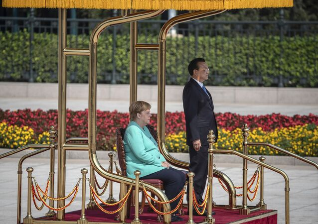 Chinese Premier Li Keqiang, right, and German Chancellor Angela Merkel listen to their countries national anthems during a welcome ceremony at the Great Hall of the People in Beijing Friday, Sept. 6,  2019