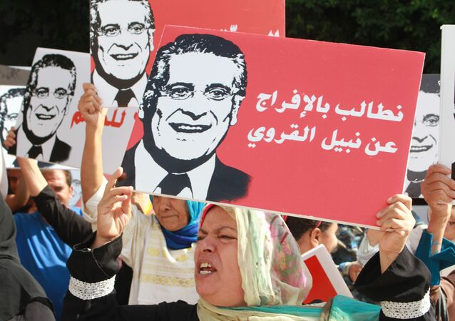 Supporters of presidential candidate Nabil Karoui carry placards with his image and slogans in his favour as they rally in front of the tribunal in the Tunisian capital Tunis asking for his release from prison on September 3, 2019.