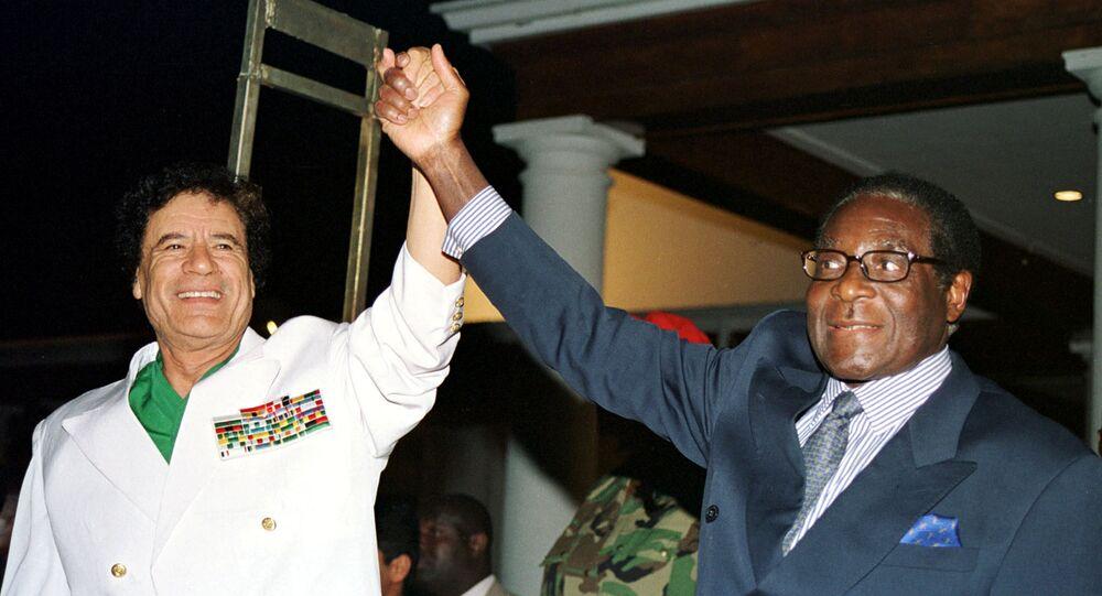 Libyan leader Colonel Muammar Gaddafi (L) and Zimbabwe President Robert Mugabe greet supporters outside State House in Harare, Zimbabwe July 12, 2001