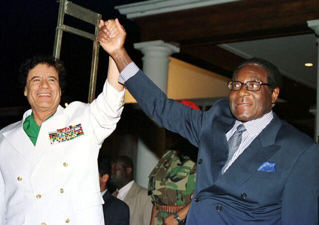 Libyan leader Colonel Muammar Gaddafi (L) and Zimbabwe President Robert Mugabe greet supporters outside State House in Harare, Zimbabwe July 12, 2001