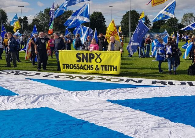 March for Scottish Independence: An SNP branch banner hovers over a large saltire with 'End London Rule' inscribed above