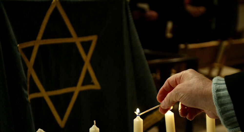 A person lights a candle during a ceremony in a synagogue