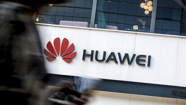 In this July 30, 2019, file photo a woman walks by a Huawei retail store in Beijing. - Sputnik International