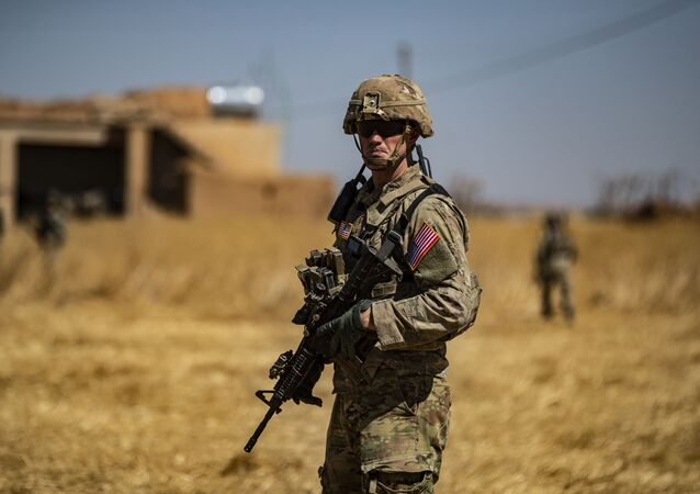 A US soldier stands guard during a joint patrol with Turkish troops in the Syrian village of al-Hashisha on the outskirts of Tal Abyad town along the border with Turkish troops, on September 8, 2019