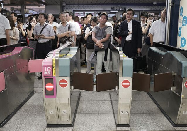 Commuters wait for automatic ticket gates to open at Shinjuku Station Monday, Sept. 9, 2019, in Tokyo. A powerful typhoon has passed over Tokyo, halting major train lines affecting morning rush-hour commuters and knocking over scaffolding and causing other damage but no reported deaths.