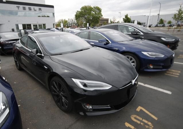 -In this Sunday, May 19, 2019, file photograph, a line of unsold 2019 Model S sedans sits at a Tesla dealership in Littleton, Colo.