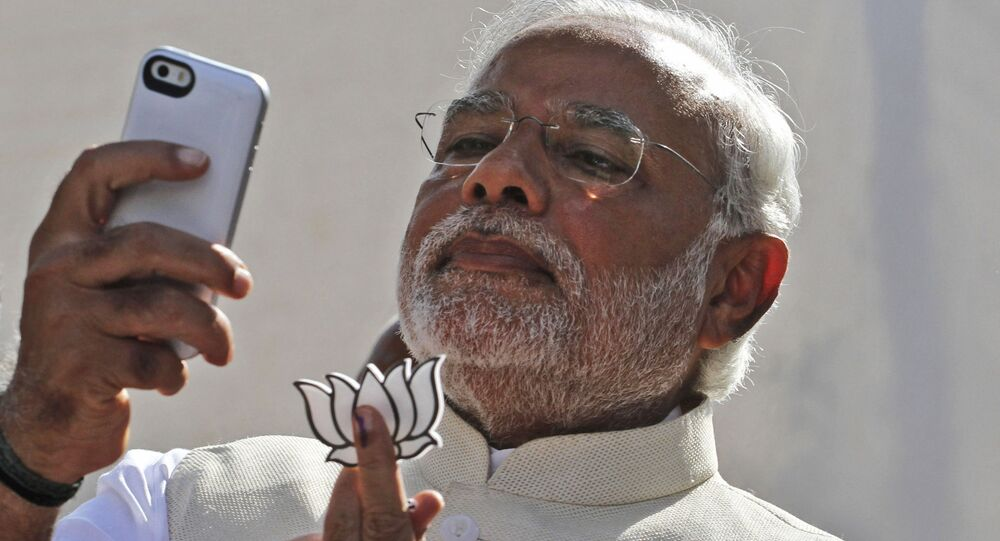 FILE- In this April 30, 2014 file photo, India's main opposition Bharatiya Janata Party's prime ministerial candidate Narendra Modi holds his party's symbol and looks into his phone after casting his vote in Ahmadabad, India