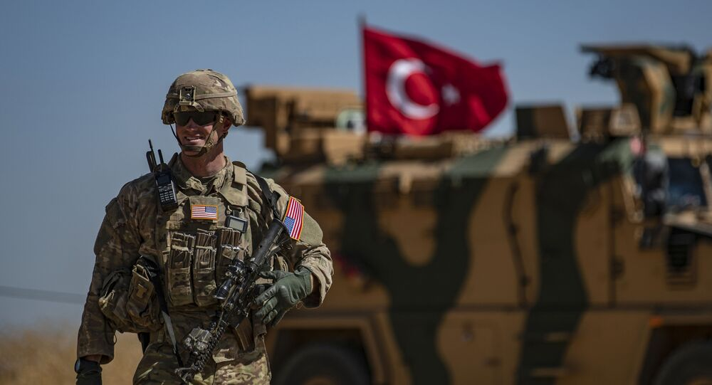 A US soldier stands guard during a joint patrol with Turkish troops in the Syrian village of al-Hashisha on the outskirts of Tal Abyad town along the border with Turkey, on September 8, 2019.