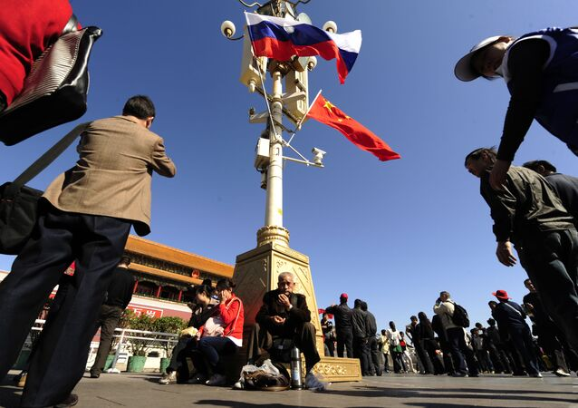 People sit under Chinese and Russian flags flying at Tiananmen Gate  (File)