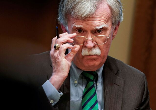 National Security Advisor John Bolton adjusts his glasses as US President Donald Trump speaks while meeting with NATO Secretary General Jens Stoltenberg in the Oval Office,  2 April 2019.