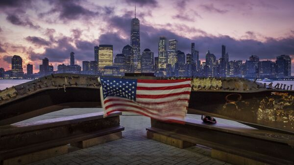 A US flag hanging from a steel girder, damaged in the 11 September 2001 attacks on the World Trade Center, blows in the breeze at a memorial in Jersey City, New Jersey on 11 September 2019. - Sputnik International