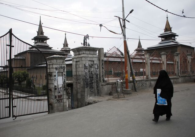 A Kashmiri woman walks past the locked Jamia Masjid (grand mosque) during restrictions, after scrapping of the special constitutional status for Kashmir by the Indian government, in Srinagar, August 26, 2019