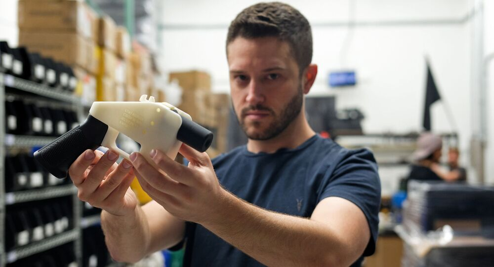 Cody Wilson, owner of Defense Distributed company, holds a 3D printed gun, called the Liberator, in his factory in Austin, Texas on August 1, 2018
