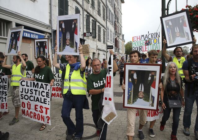 Demonstrators hold upside down portraits of French President Emmanuel Macron during a protest through the streets of Bayonne, France Sunday, Aug. 25, 2019. Critics of French President Emmanuel Macron are marching near the G-7 summit he is hosting to demand he do more to protect French workers and the planet. A melange of activists, some wearing yellow vests, carried portraits of Macron as they marched Sunday through the southwest city of Bayonne. Some held the portraits upside down.