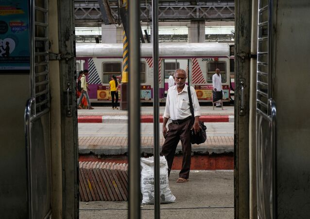 A man waits for a train at a railway station in Mumbai.