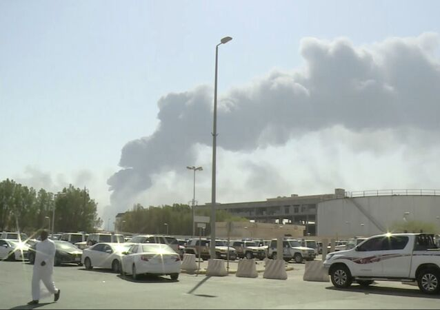 In this image, made from a video broadcast on the Saudi-owned Al-Arabiya satellite news channel on Saturday, 14 Sept. 2019, a man walks through a parking lot as the smoke from a fire at the Abqaiq oil processing facility can be seen behind him in Buqyaq, Saudi Arabia. Drones launched by Yemen's Houthi rebels struck the world's largest oil processing facility in Saudi Arabia and another major oil field Saturday, sparking huge fires at a vulnerable chokepoint for global energy supplies.