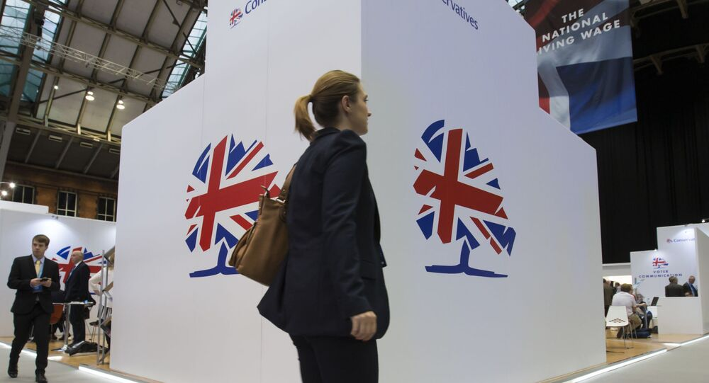 A delegate walks past a Conservative Party logo sign at Britain's annual Conservative Party Conference.