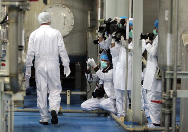 Cameramen and photographers take pictures as an Iranian technician walks through the Uranium Conversion Facility just outside the city of Isfahan 255 miles (410 kilometers) south of the capital Tehran, Iran, Saturday, Feb. 3, 2007