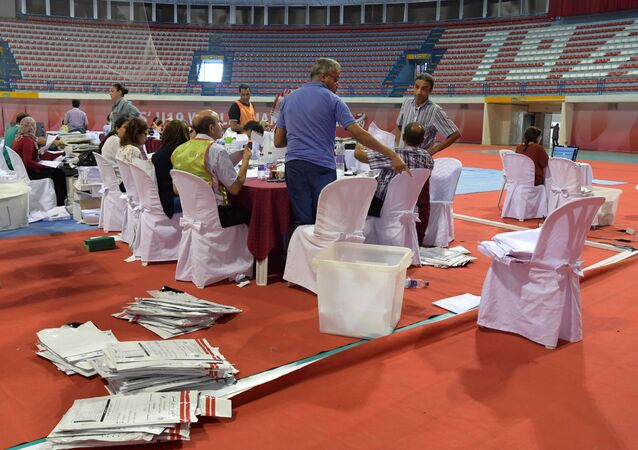 Staff members of Tunisia's Independent Higher Authority for Elections (ISIE) sort through ballots as they prepare the results of the presidential vote at a sorting center in Ariana, north of the capital Tunis on September 16, 2019.