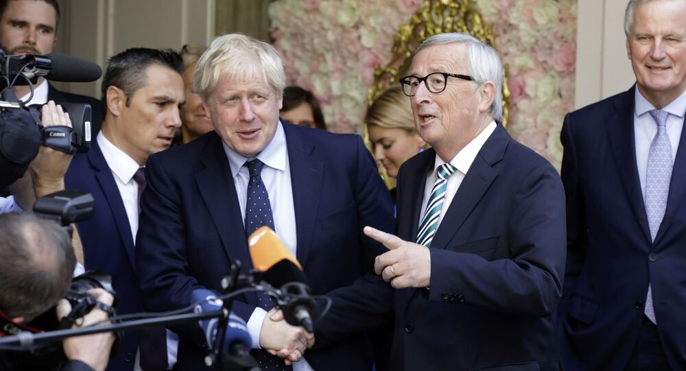 European Commission President Jean-Claude Juncker, center right, speaks with the media as he shakes hands with British Prime Minister Boris Johnson prior to a meeting at a restaurant in Luxembourg, Monday, Sept. 16, 2019
