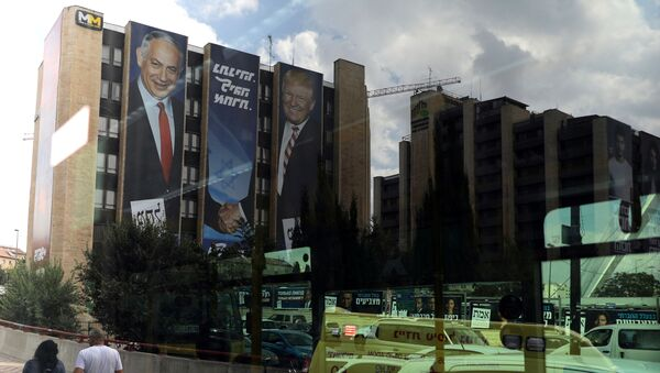 A reflection in a bus window shows a Likud party election campaign banner depicting Israeli Prime Minister Benjamin Netanyahu shaking hands with U.S. President Donald Trump in Jerusalem 15 September 2019. - Sputnik International