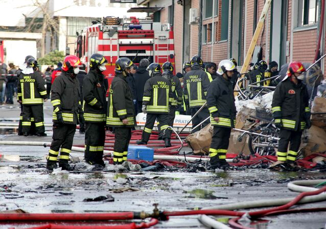 Firefighters inspect the area where a fire broke out in a Chinese-run garment factory in Prato, near Florence, Italy, Sunday, Dec. 1, 2013