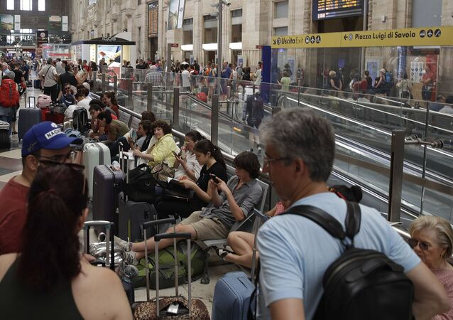 People wait inside Milan's Central railway Station