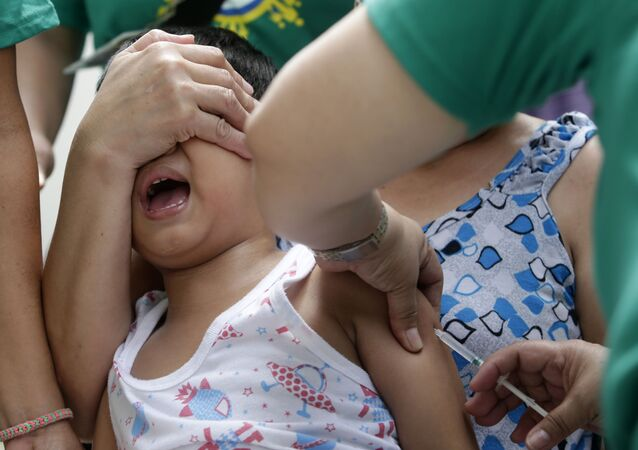 A local health worker administers a vaccine at a local health center at the financial district of Makati, east of Manila, Philippines, Friday, Sept. 12, 2014.