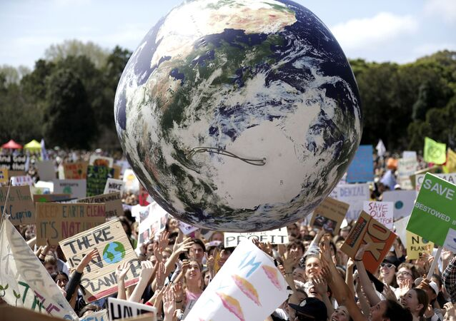 A large inflatable globe is bounced through the crowd as thousands of protestors, many of them school students, gather in Sydney, Friday, Sept. 20, 2019