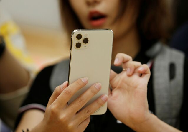 A woman holds an iPhone 11 Pro Max while giving a live broadcast after it went on sale at the Apple Store in Beijing, China, September 20, 2019