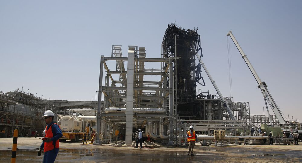 In this photo opportunity during a trip organized by Saudi information ministry, a worker walks in front of the Khurais oil field in Khurais, Saudi Arabia, Friday, Sept. 20, 2019, after it was hit during Sept. 14 attack.