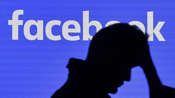 A man passes a facebook screen - Sputnik International