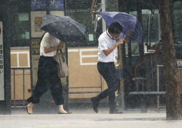 Pedestrians try to hold their umbrellas while struggling with strong winds