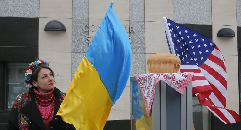 A woman holds a Ukraine flag and looks up at the traditional Ukrainian bread and salt in front of the US embassy in Kiev, Ukraine, Friday, Jan. 20, 2017, in support of Donald Trump hours before he is to be sworn in as president of the United States.