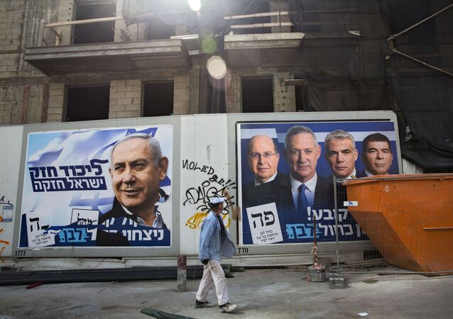 A man walks by election campaign billboards showing Benjamin Netanyahu, left, alongside the Blue and White party leaders