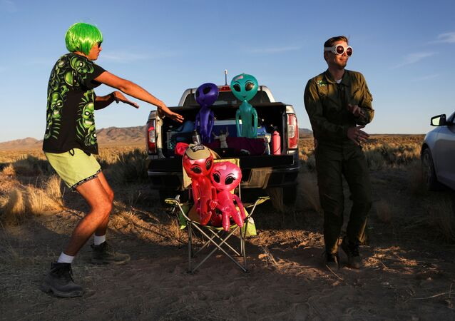 FILE PHOTO: Two men dance on a road to an entrance to Area 51 as an influx of tourists responding to a call to 'storm' Area 51, a secretive U.S. military base believed by UFO enthusiasts to hold government secrets about extra-terrestrials, is expected in Rachel, Nevada, U.S. September 20, 2019. REUTERS/Jim Urquhart/File Photo