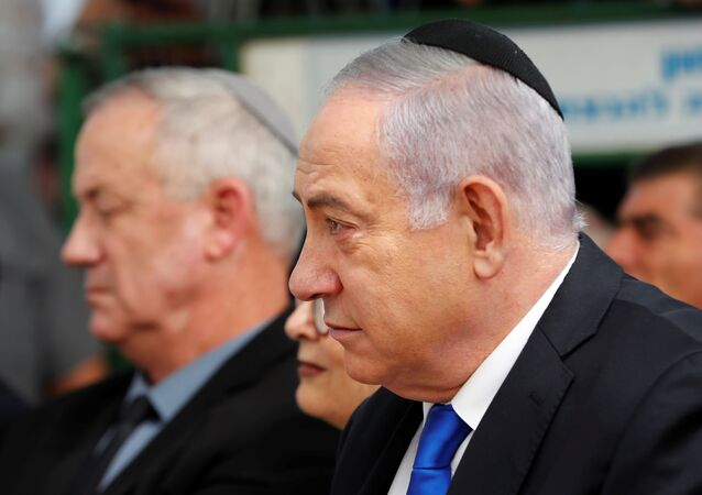 Israeli Prime Minister Benjamin Netanyahu looks on as he sits next to Benny Gantz, leader of Blue and White party, during a memorial ceremony for late Israeli President Shimon Peres, at Mount Herzl in Jerusalem September 19, 2019. REUTERS/Ronen Zvulun