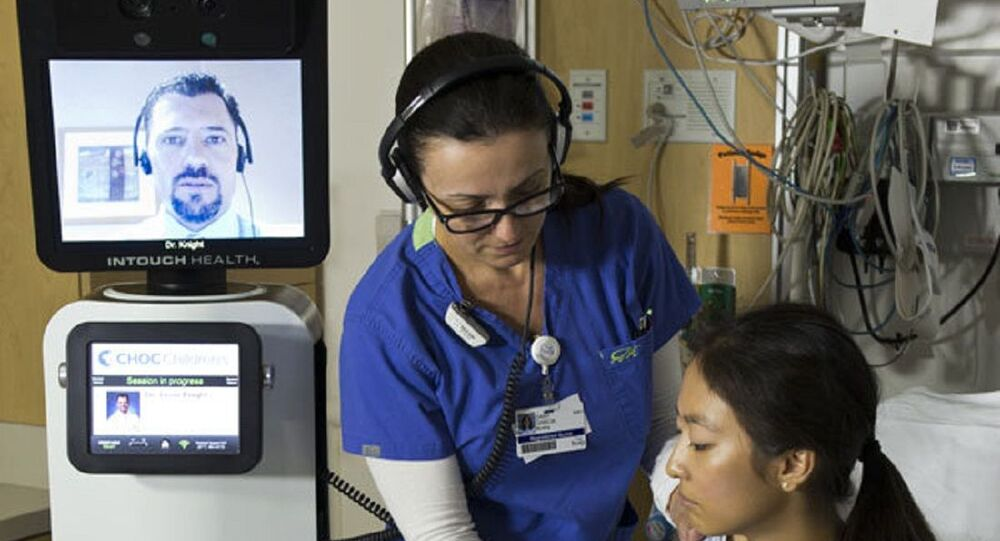 A nurse checks a patient's vitals during a consultation by the RP-VITA robotic doctor