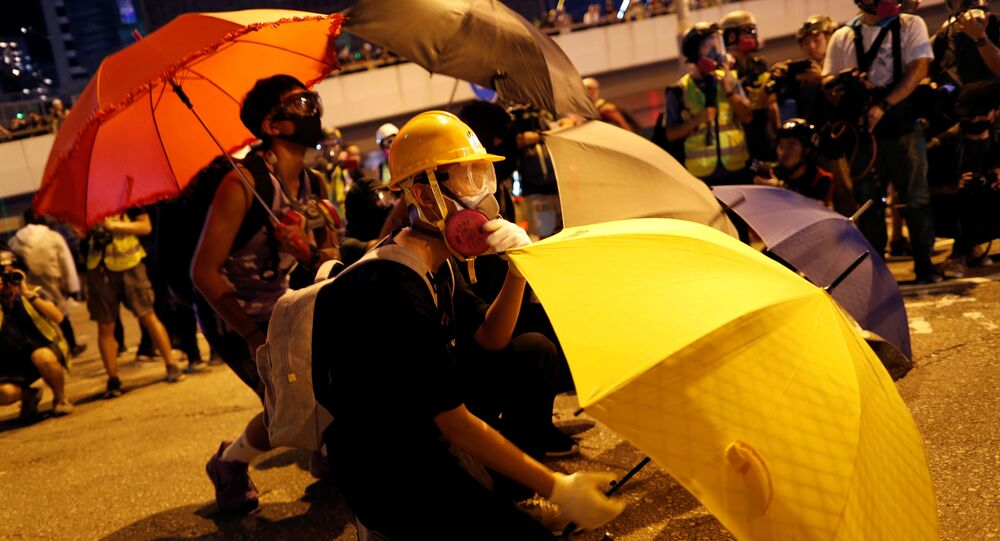 An anti-government protester shelters behind an umbrella as he attends a rally outside the Legislative Council building in Hong Kong, China 28 September 2019.