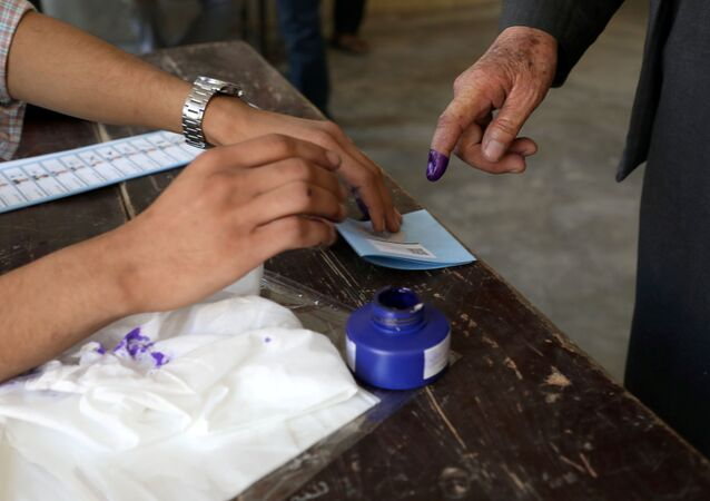 An election official assists an Afghan man at a polling station in Kabul, Afghanistan 28 September 2019.
