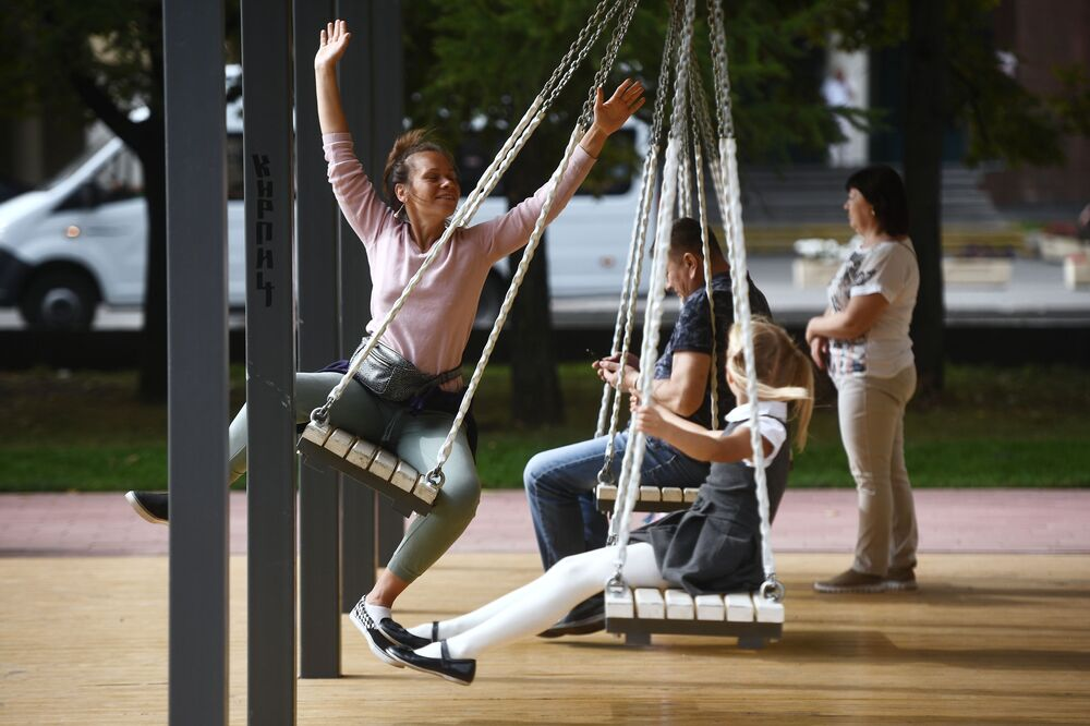 People having a rest on a swing on a Moscow boulevard.